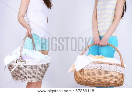 Women holding laundry baskets with clean clothes, towels and pins, on gray background