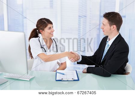 Doctor Greeting Businessman In Clinic