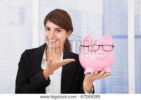 Businesswoman Showing Piggybank With Eyeglasses