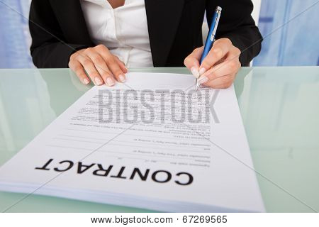 Businesswoman Signing Contract Paper At Desk
