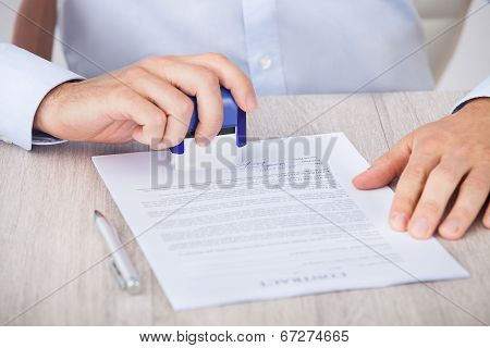 Cropped Image Of Businessman Stamping Contract Paper