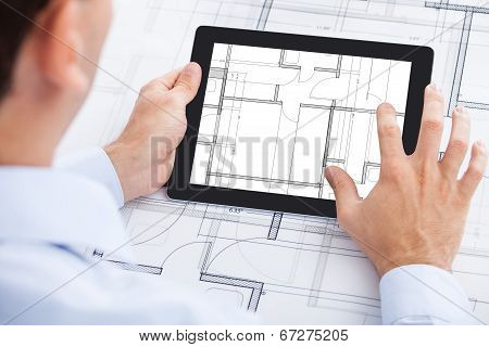 Architect Analyzing Blueprint On Digital Tablet