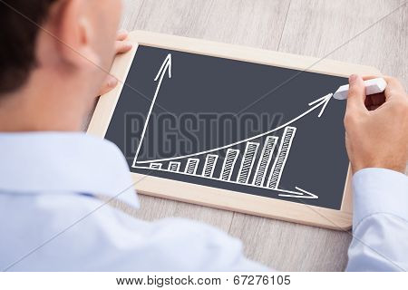Businessman Drawing Bargraph On Slate At Desk