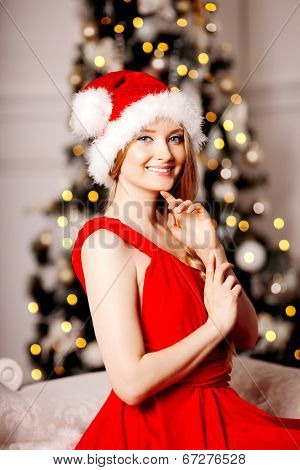 Young beautiful smiling santa woman near the Christmas tree. Fashionable luxury girl celebrating New Year. Beauty luxury trendy blonde.
