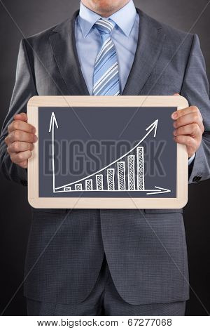 Businessman Showing Bargraph Drawn On Slate