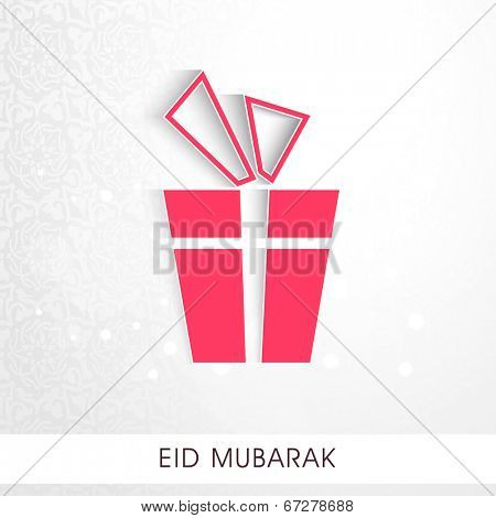 Beautiful pink gift boo wrapped in white ribbon on grey background for Eid Mubarak celebrations.