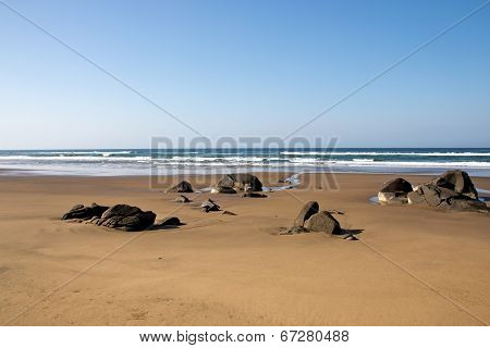 Rocks Protruding From Sandy Beach At Low Tide