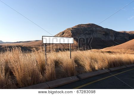 Road Sign Amidst Long Dry Grass In Dry Winter Landscape