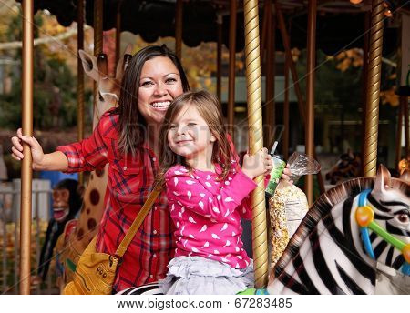 a young mother and her daughter riding on a merry go round at t