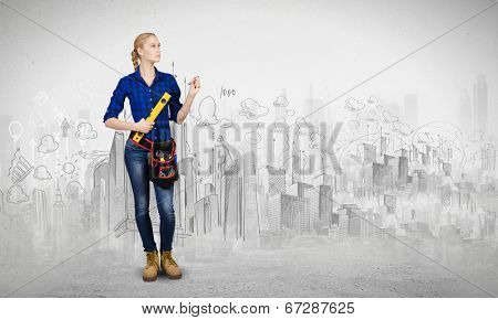 Young woman mechanic with ruler in hand against city background