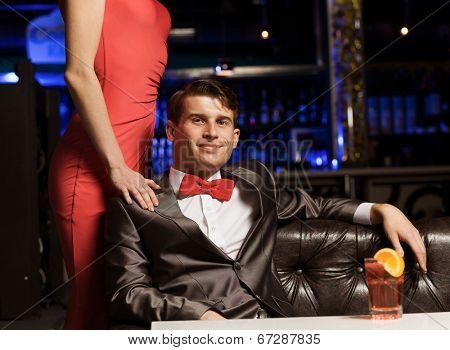Young handsome man in bar accompanied by elegant lady