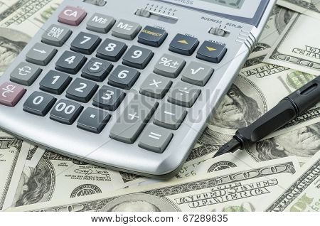 Pen and Calculator on a background of american dollar bills