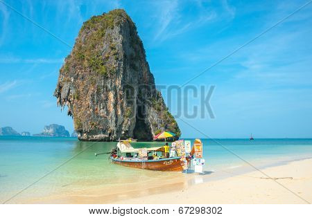 RAILAY, THAILAND - MARCH 19, 2014: Tourist merchant long tail boat on tropical pranang beach with limestone rock Railay Krabi  Thailand