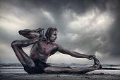 image of dhanurasana  - Man doing Yoga on the beach at overcast dramatic sky in India - JPG
