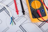 stock photo of multimeter  - Closeup of multimeter with wires on blueprint - JPG