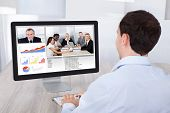 stock photo of video chat  - Rear view of businessman video conferencing with colleagues on desktop PC at office desk - JPG