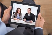 foto of video chat  - High angle view of businessman video conferencing with colleagues on digital tablet in office - JPG