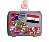 stock photo of iraq  - Used plastic suitcase with lots of small stickers large sticker of Iraq - JPG