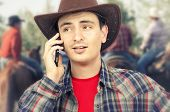 stock photo of ironic  - Face portrait of young cowboy talking on smartphone with ironic smile on rodeo background - JPG
