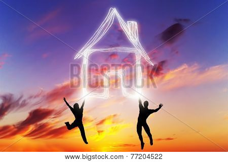 Happy couple jump and make a house symbol of light. Dreaming about new home, mortgage, new life together. Sunset sky