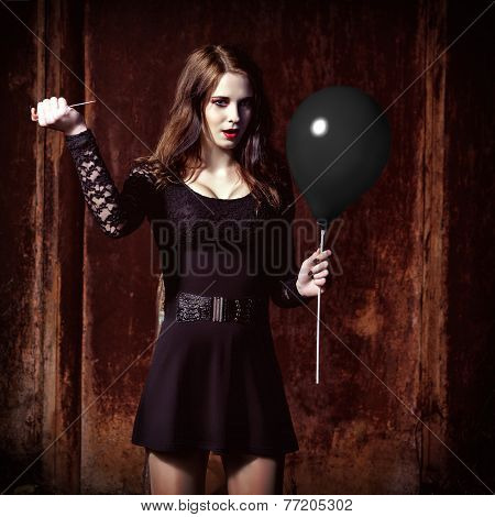 Weird Angry Girl Is Piercing A Black Balloon By Needle