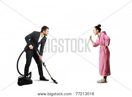 smiley man in suit holding vacuum cleaner and looking at screaming angry wife in pink dressing gown. isolated on white