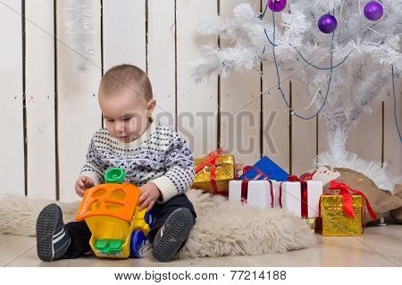 Baby boy under Christmas fir tree