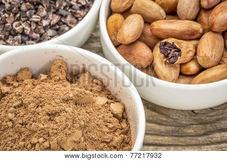 cacao beans, nibs and powder in white ceramic bowls against grained wood
