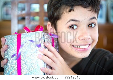 Excited young boy holding a wrapped up Christmas present