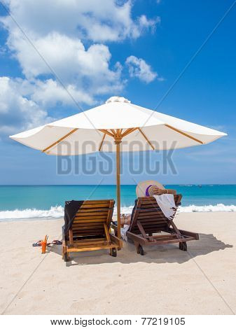 Lady in white hat sitting in chaise longue in Bali Indonesia
