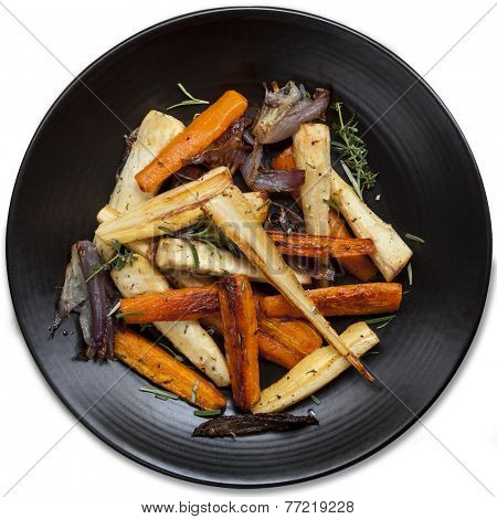 Roasted root vegetables in black platter, isolated.  Top view.