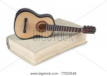 Old book and guitar on a white background