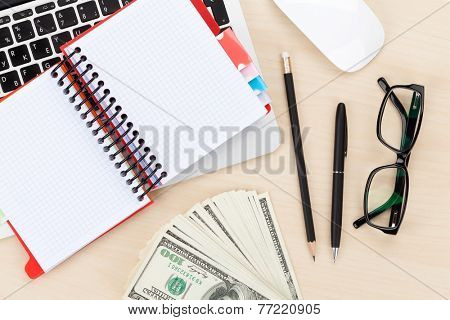 Office table with computer, supplies and money cash. View from above with notepad for copy space