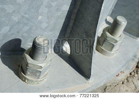 Close up of some larger screws into the base of a metal pillar.