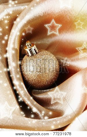 Beautiful Christmas ball on golden satin cloth