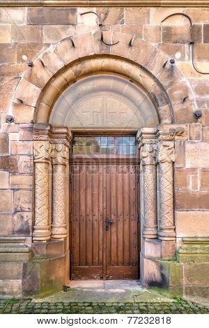 Wooden door in a romanesque stepped portal
