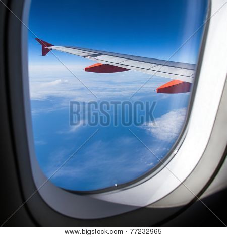 Clouds and sky seen through window of an aircraft