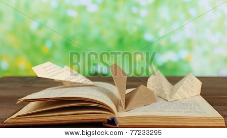 Origami airplanes on old book, on wooden table, outdoors