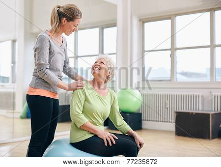 Older Woman Assisted By Personal Trainer At Gym