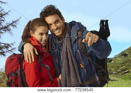 Happy young couple outing on sunny day wearing trekking clothes.