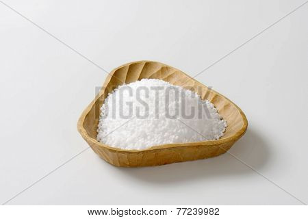 handmade wooden bowl full of coarse grained salt