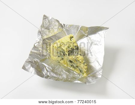 overhead view of unwrapped triangle of blue cheese in the aluminum foil