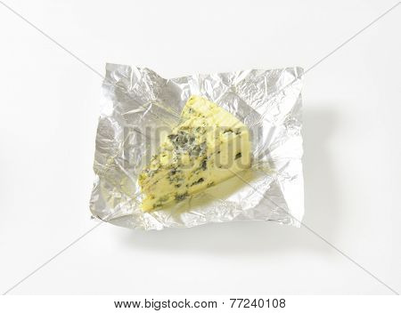 piece of Roquefort cheese in the aluminum wrapper