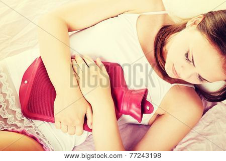 Beautiful young woman is lying on the bed with hot water bottle, have stomach ache.