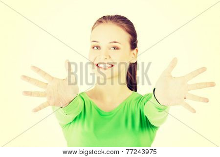 Attractive  woman with hands open in front oh her. Isolated on white.