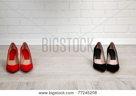 Red and black women shoes with  on the floor