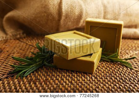 Rosemary handmade soap with the branches of rosemary on sackcloth, on wooden background