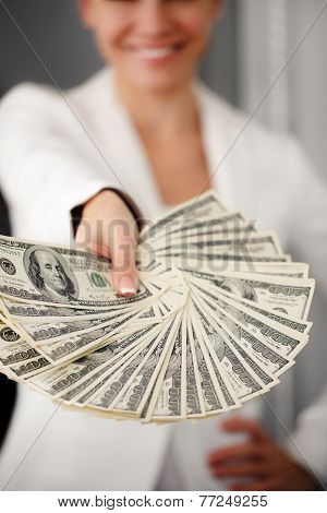 portrait of a pretty brunette girl giving money isolated