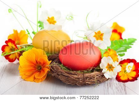 Easter egg in nest with spring flowers
