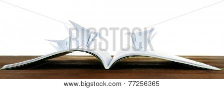 Origami cranes on notebook on wooden table, on white background